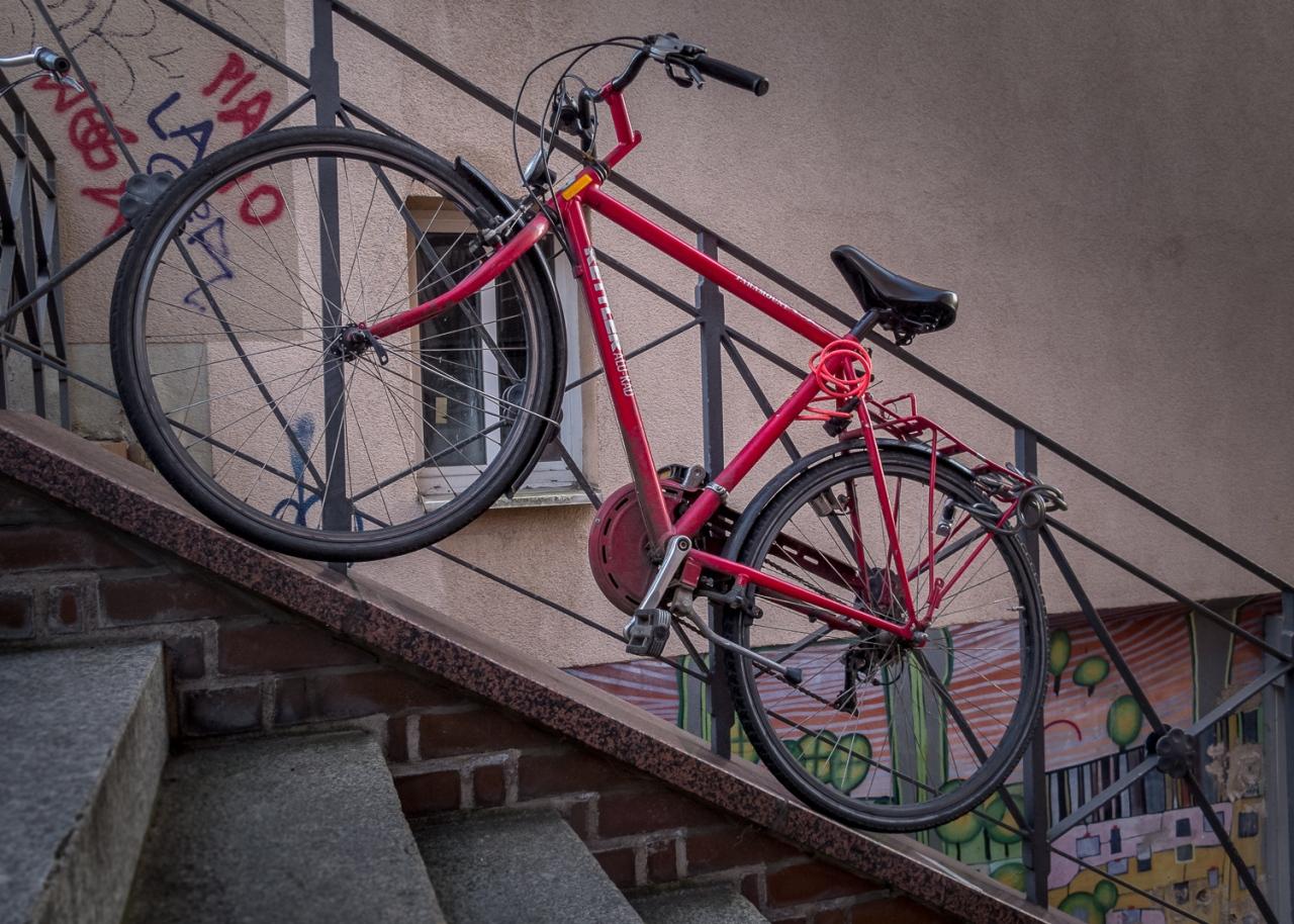 rotes Fahrrad an steilem Treppengeländer angeschlossen