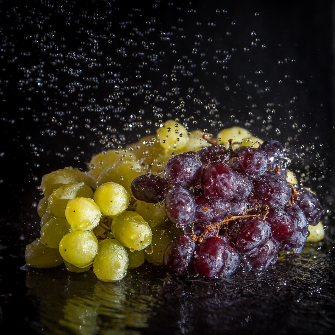 Weintrauben auf schwarzem Untergrund im Waserstrahl