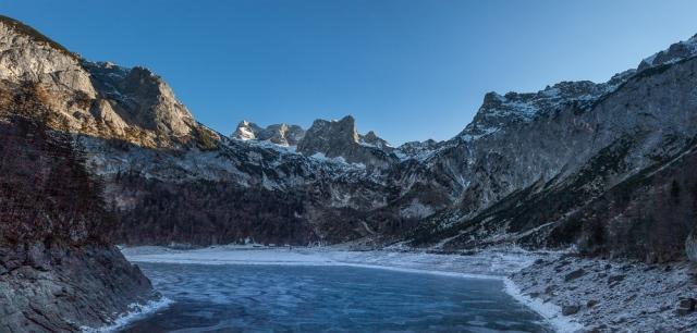 Der hintere Gosausee ist komplett zugefroren. Im Hintergrund das eindrucksvolle Dachsteinmassiv über einer bewirtschafteten Alm am Seeende.